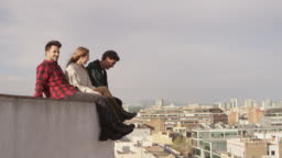 Young friends talking while sitting at terrace