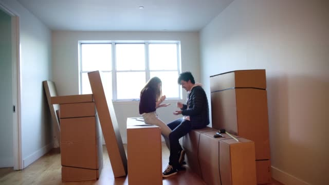 young friends, teenagers girl and boy, playing, sitting on the card boxes in the living room of the new house. - house rental stock videos & royalty-free footage