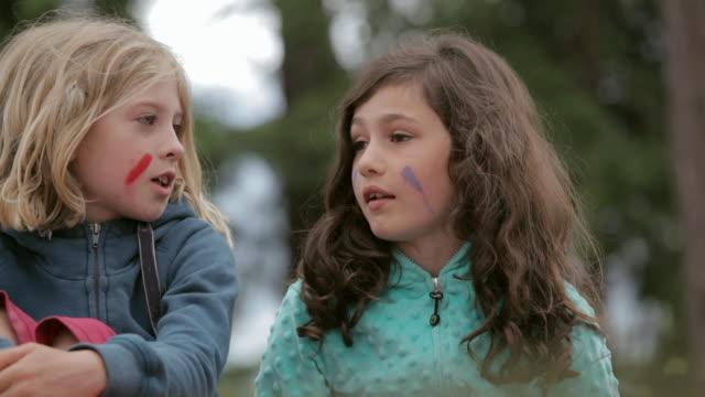 tu young friends wearing face paint chatting in the woods / vancouver, british columbia, canada - skvaller bildbanksvideor och videomaterial från bakom kulisserna