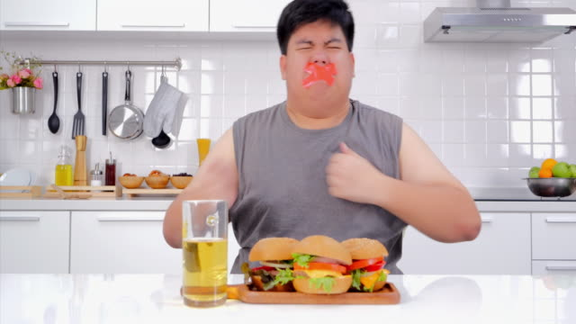 young frustrated man with a measuring tape around his mouth junk food shaped.man on diet with a guilty conscience.diet restriction stress concept.real bodies - forbidden stock videos & royalty-free footage