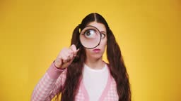 Young funny attractive caucasian girl with long braids holding a magnifying glass in front of camera and makes faces and grimaces on yellow backgorund. Human curiosity search concept