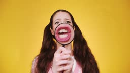 Young funny attractive caucasian girl with long braids holding and play magnifying glass in front of camera and makes faces and grimaces on red backgorund. Comic humor theme with magnifying face
