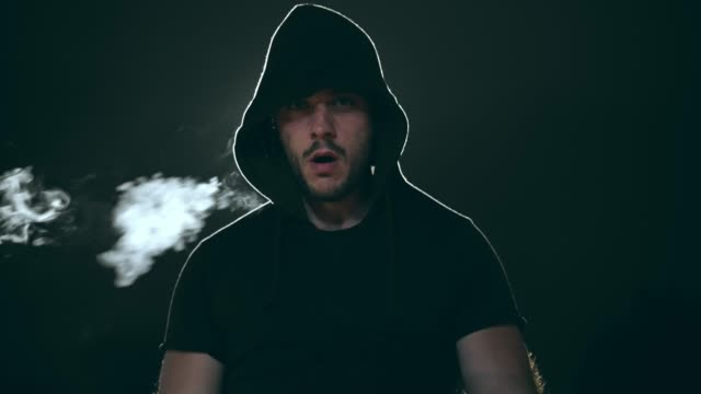 Young gangster troublemaker smoking a cigarette and looking at camera outdoors at night