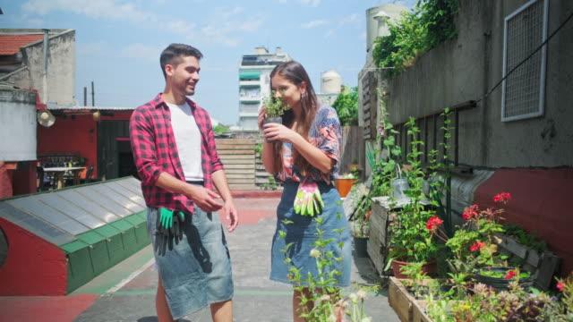 vidéos et rushes de jeunes passionnés de jardinage vérifiant l'arôme de plante - partage