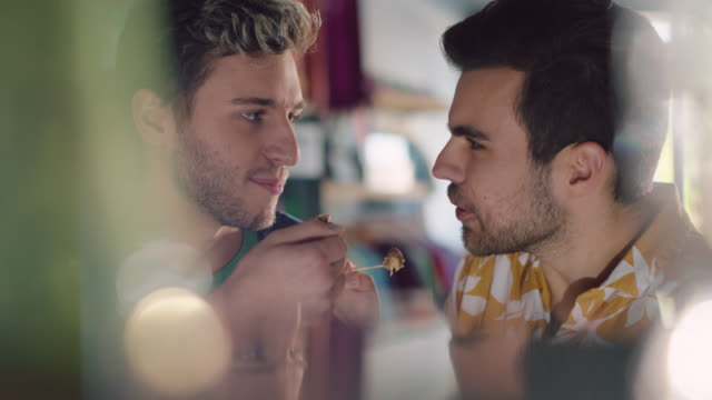 vídeos y material grabado en eventos de stock de slo mo. young gay couple eats ice cream together at an ice cream parlor - masticar