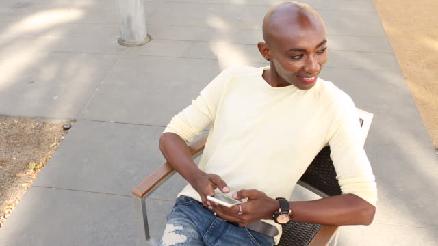 a young gay man using a cellular device outdoors on a sunny day. - ermafrodita video stock e b–roll