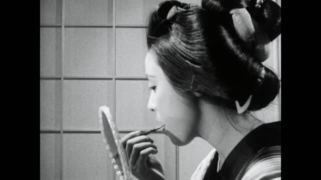 young geisha woman applies lip color in hand mirror; 1964 - bbc archive stock-videos und b-roll-filmmaterial
