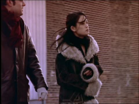 young generation x couple in coats walking outdoors in nyc - x世代点の映像素材/bロール