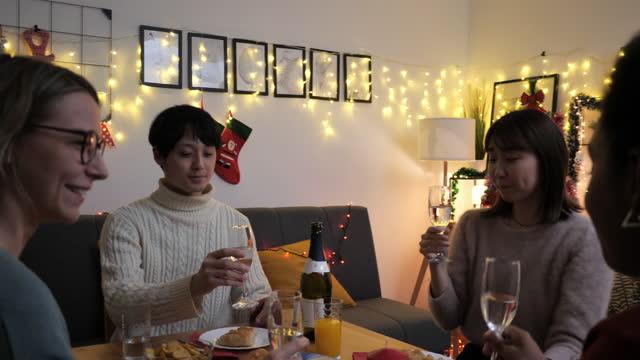 stockvideo's en b-roll-footage met jonge generatie z vrienden thuis bij het diner van kerstmis, het opheffen van de toost - generation z