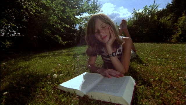 A young German girl lies on the ground and reads a book