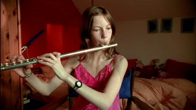A young German girl plays the flute.