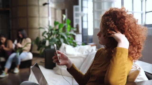 vídeos de stock, filmes e b-roll de mulher nova do gengibre que usa dispositivos portáteis, tendo a chamada video da família - estudante universitária
