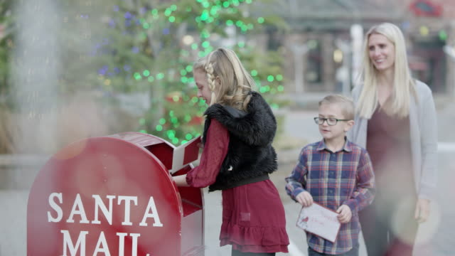 young girl and boy put letters in mailbox to santa claus - letterbox stock videos & royalty-free footage