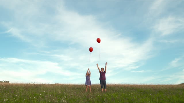 mws young girl and boy releasing balloons in field  - releasing stock videos & royalty-free footage