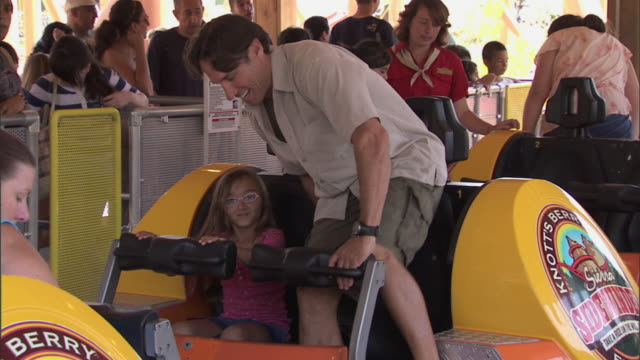 young girl and father take seats on sidewinder roller coaster at knott's berry farm - anticipation stock videos and b-roll footage