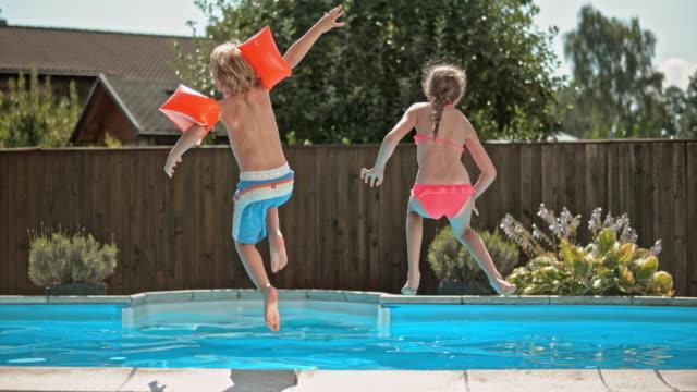 vidéos et rushes de au ralenti ds sœurs sauter dans la piscine avec petit frère - clôture jardin