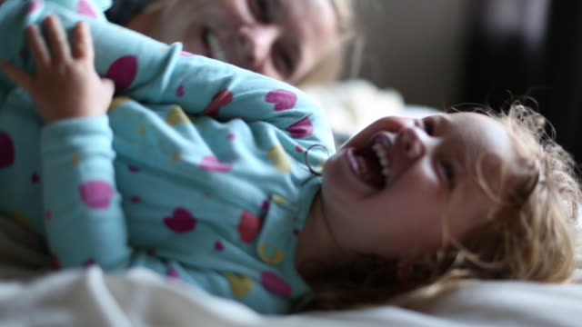 a young girl and her mom playing together on a bed. - kitzeln stock-videos und b-roll-filmmaterial