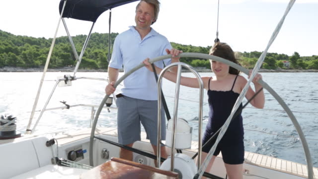 young girl at helm of yacht with dad's guidance. - tutina video stock e b–roll