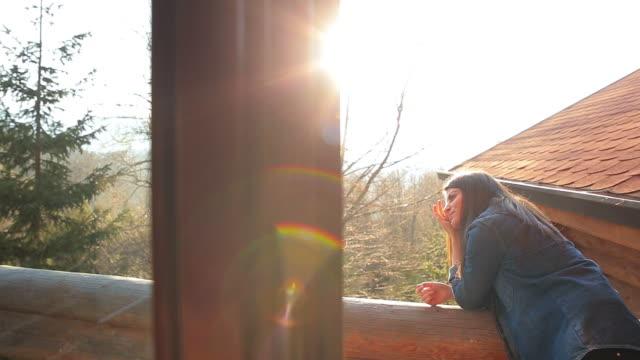 vídeos de stock e filmes b-roll de rapariga na varanda de cabina admirar a bela vista. - cabana de madeira