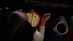 Young girl at the movies enjoying popcorn while watching a 3D movie
