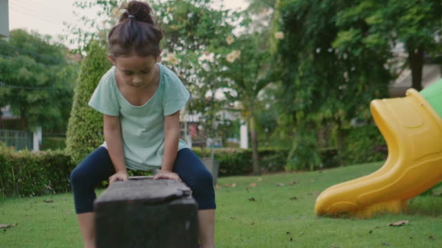 Young Girl Balances in garden.