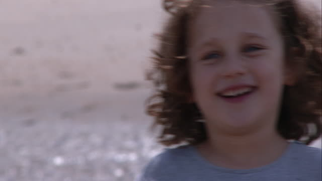 vidéos et rushes de young girl being goofy on the beach in sandy hook - vue de face