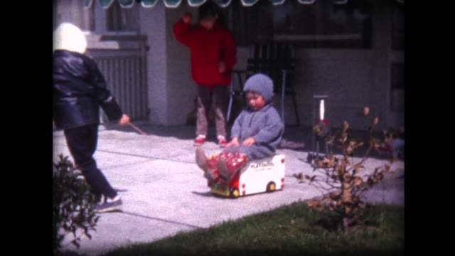 1962 young girl being pulled on toy and blowing kisses - 1962 stock-videos und b-roll-filmmaterial