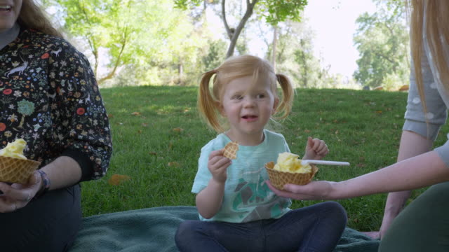vidéos et rushes de young girl biting a waffle cone bowl deciding if she likes the flavor - tante