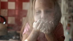 Young girl blowing flour in kitchen