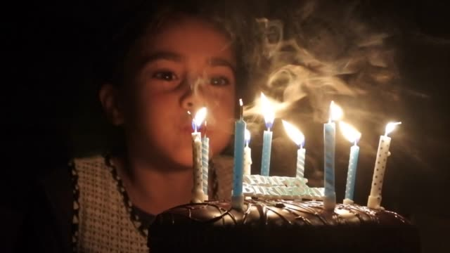 young girl blowing her birthday cake candles - soffiare video stock e b–roll