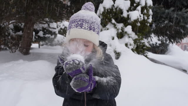 young girl blowing snow out of hands - mitten stock videos and b-roll footage