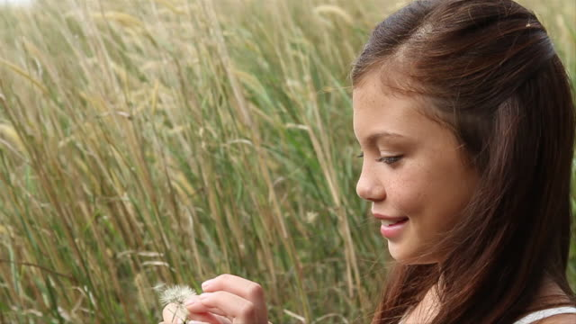 A young girl blows on a dandelion in a grassy field.