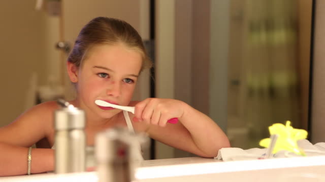 cu young girl brushing her teeth in bathroom / lamy, new mexico, united states - borsta tänder bildbanksvideor och videomaterial från bakom kulisserna