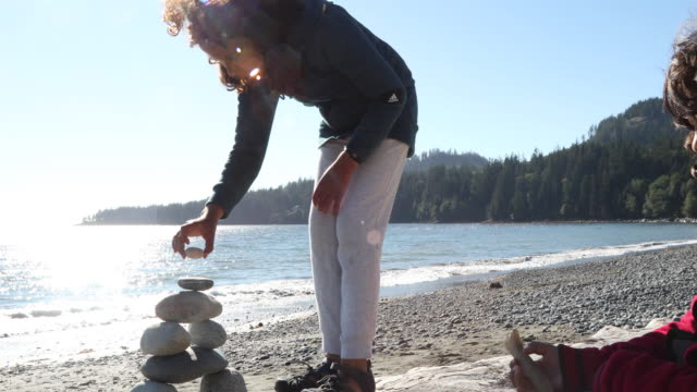 young girl builds inukshuk on log while sister looks on - north american tribal culture stock videos & royalty-free footage