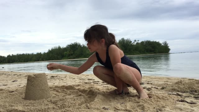 Young girl builds sand castled on a tropical pacific island beach