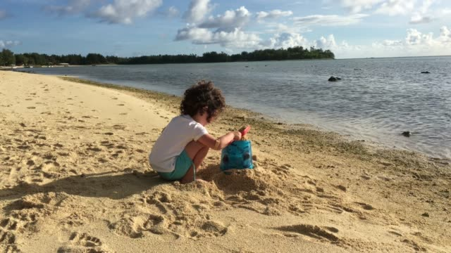 young girl builds sand castled on a tropical pacific island beach - cook islands stock videos & royalty-free footage