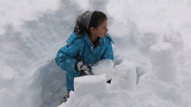young girl builds snow fort, in deep drift - digging stock videos & royalty-free footage