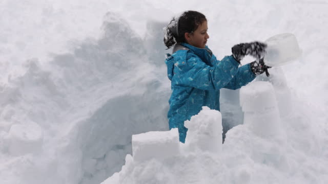 young girl builds snow fort, in deep drift - fortress stock videos & royalty-free footage