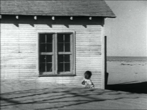 vidéos et rushes de pan young girl carrying bucket past house to cart in dust bowl / oklahoma - 1936