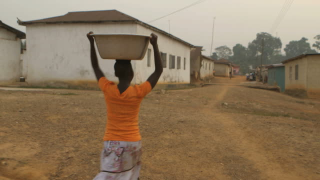 stockvideo's en b-roll-footage met young girl carrying water on her head in african village - meisjes