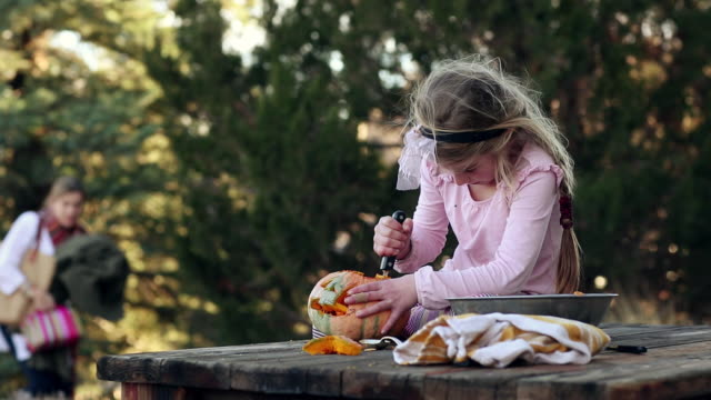 MS Young girl carving pumpkin and her mother looking / Lamy, New Mexico, United States