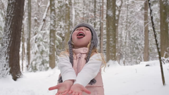 young girl catching snowflakes on her tongue - mitten stock videos and b-roll footage