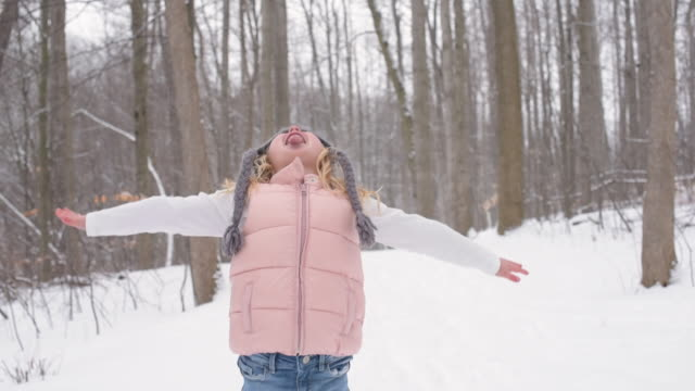 young girl catching snowflakes on tongue - mitten stock videos and b-roll footage