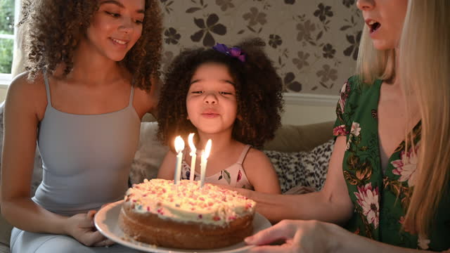 young girl celebrating birthday with mother and older sister - candid stock videos & royalty-free footage