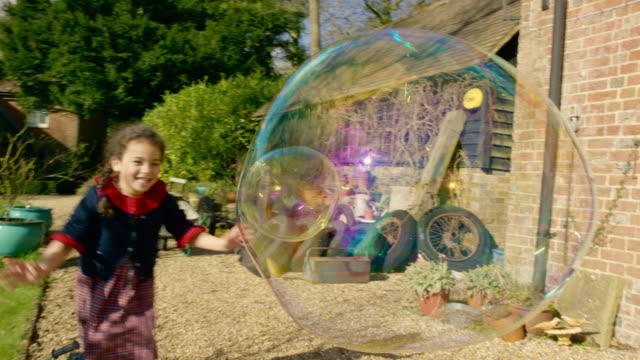 Young girl chasing large bubbles in garden