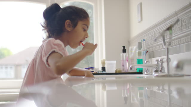 vidéos et rushes de young girl cleaning her teeth in the bathroom - lavabo