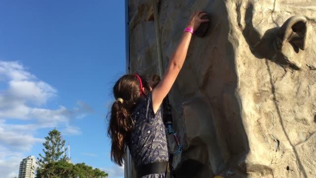 Young Girl Climbing on a Climbing Wall Outdoors