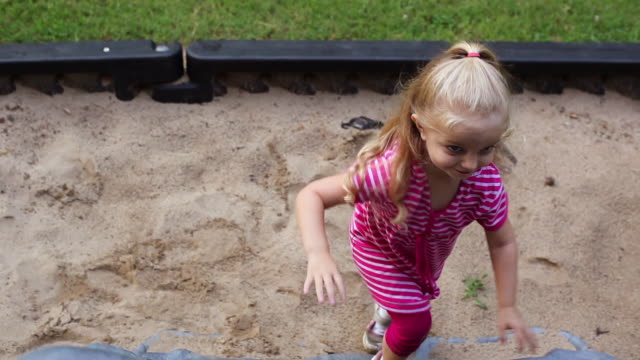 young girl climbs up play-set and smiles with a sandbox underneath her - sand pit stock videos and b-roll footage