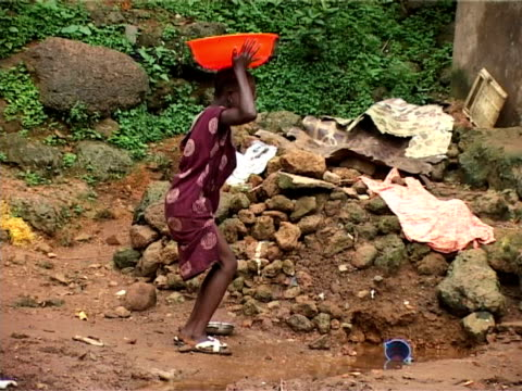 vidéos et rushes de young girl collecting water, kroo bay, freetown, sierra leone - carrying