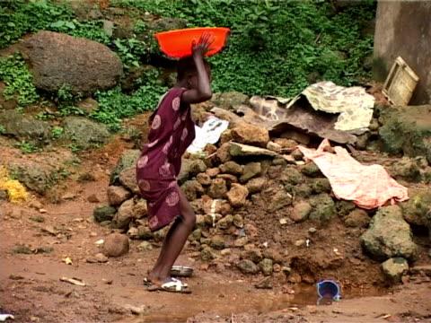 stockvideo's en b-roll-footage met young girl collecting water, kroo bay, freetown, sierra leone - alleen meisjes